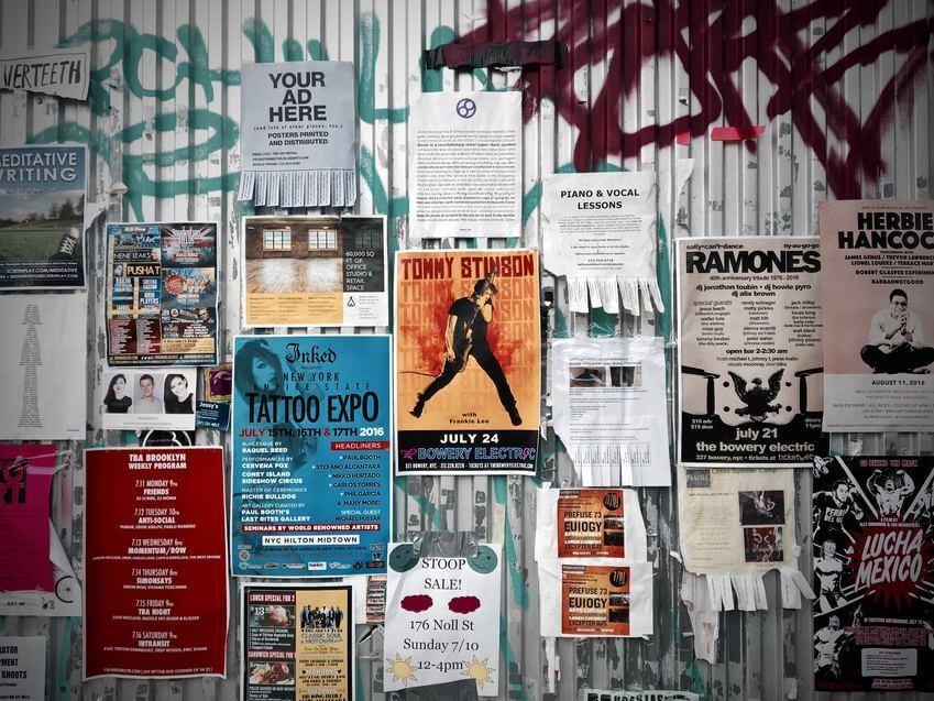 Numerose locandine affisse su parete